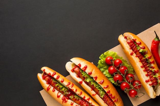 Deliciosos cachorros-quentes e tomates