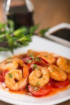Deliciosos camarões cozidos com tomate no prato branco