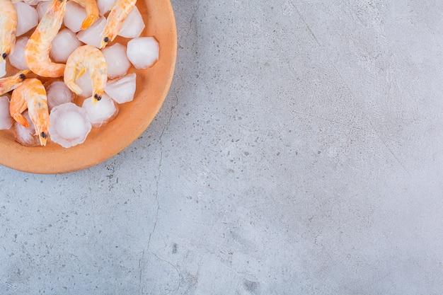 Deliciosos camarões em cubos de gelo em um prato laranja sobre uma superfície de pedra