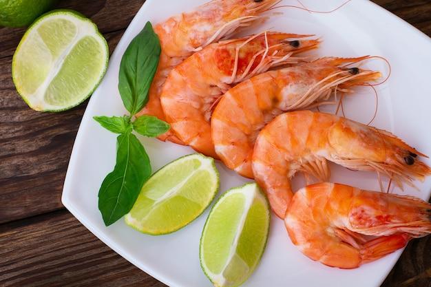 Deliciosos camarões frescos com limão na mesa de madeira