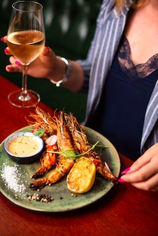 Deliciosos camarões lagostins em restaurante em mesa de madeira saborosos frutos do mar com vinho no menu do café