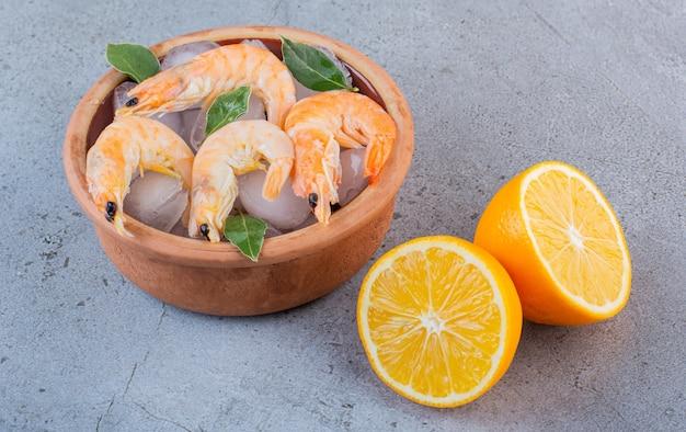 Deliciosos camarões no gelo com folhas de louro em uma tigela de barro sobre um fundo de pedra.