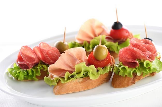Deliciosos canapés baguetes com folhas de salame de alface ou mussarela de tomate com presunto de parma e azeitona