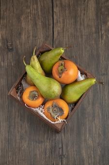 Deliciosos caquis fuyu e peras maduras em caixa de madeira
