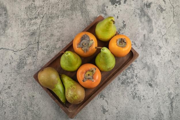 Deliciosos caquis fuyu e peras maduras em um prato de madeira