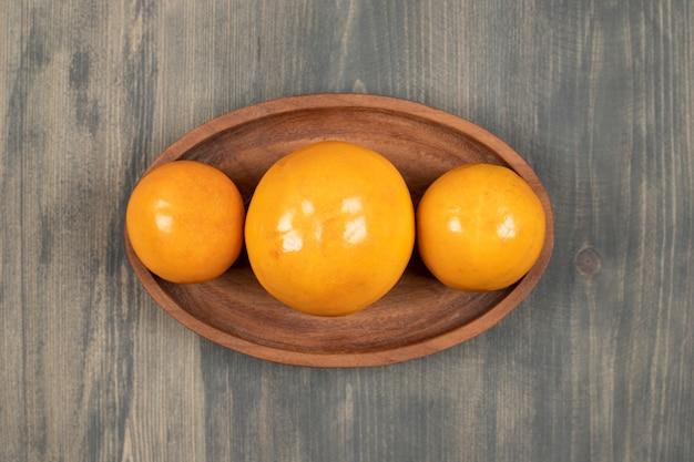 Deliciosos caquis suculentos em uma placa de madeira