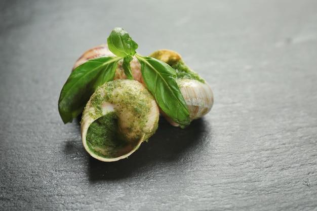 Deliciosos caracóis em molho verde na mesa escura
