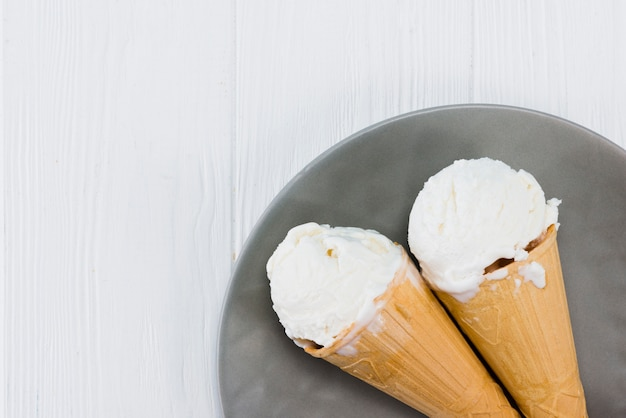 Deliciosos casquinhas de sorvete no prato na mesa de madeira