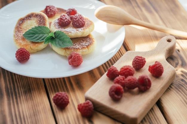 Deliciosos cheesecakes ou panquecas polvilhadas com açúcar de confeiteiro na chapa branca na mesa de madeira com framboesas e folha de hortelã