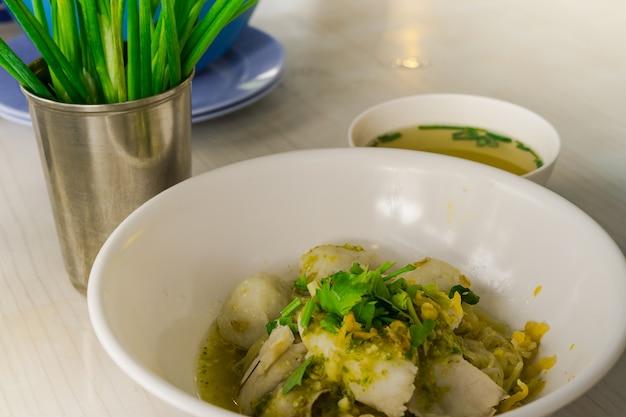 Deliciosos chinelos amarelos chinês com bola de peixe em branco tigela para fundo de comida