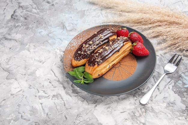 Deliciosos choco eclairs com morangos em uma mesa clara e bolo de biscoito de sobremesa