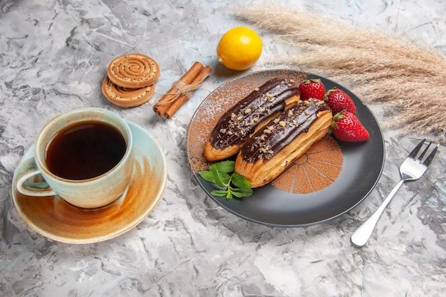 Deliciosos choco eclairs com uma xícara de chá na mesa clara e bolo de biscoito de sobremesa