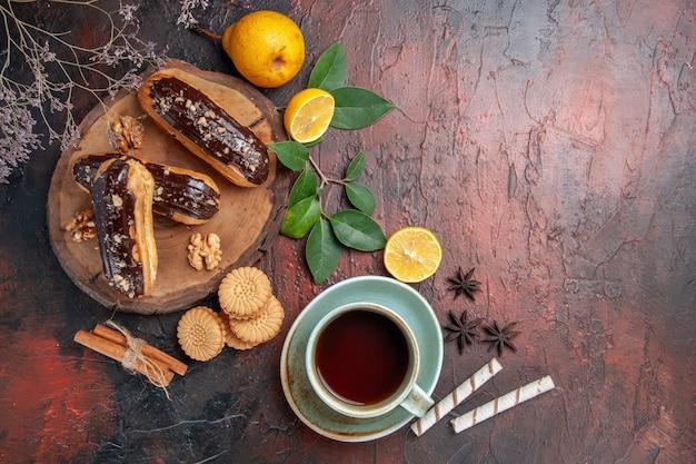 Deliciosos choco eclairs de cima com uma xícara de chá na mesa escura e bolos doces