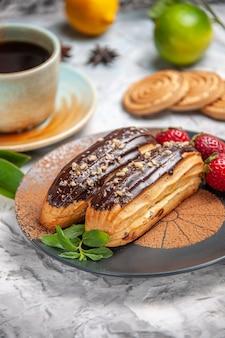 Deliciosos choco eclairs de frente para o chá no bolo de sobremesa de biscoito de mesa branca