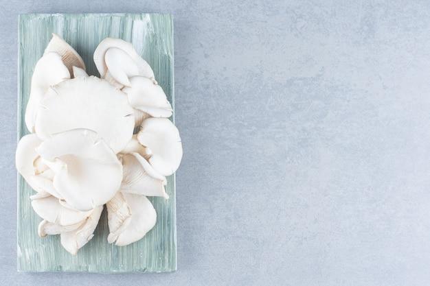 Deliciosos cogumelos ostra orgânicos em fundo cinza.