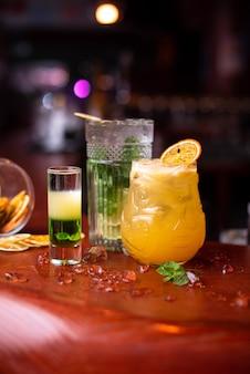 Deliciosos coquetéis de verão frio com limão, hortelã e gelo em um copo com gotas. coquetel de álcool multicolorido no bar.