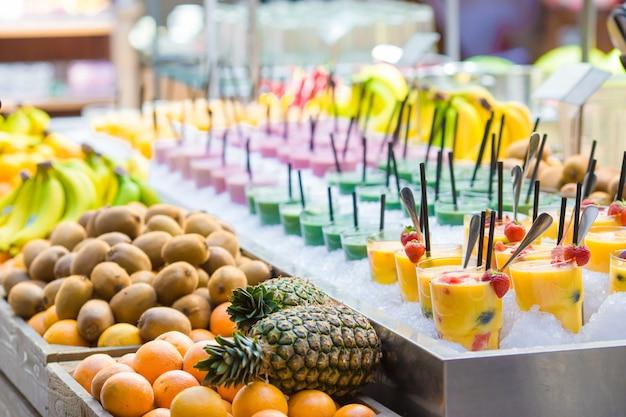 Deliciosos coquetéis doces e frutas frescas na loja com comida para levar