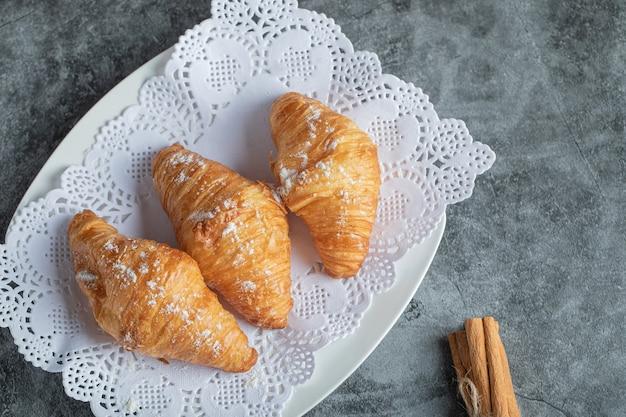 Deliciosos croissants com paus de canela em cinza.
