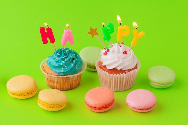 Deliciosos cupcakes com velas em um fundo colorido.