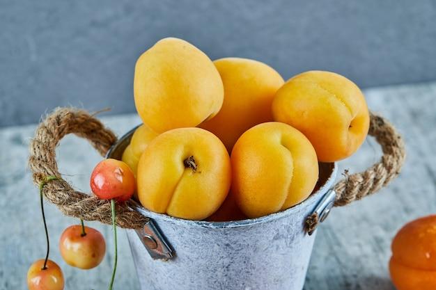 Deliciosos damascos maduros em balde de ferro com cerejas na superfície de mármore