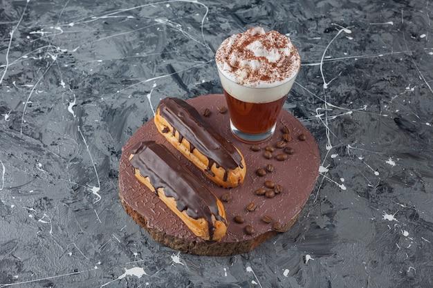 Deliciosos doces de chocolate eclairs e café na peça de madeira.