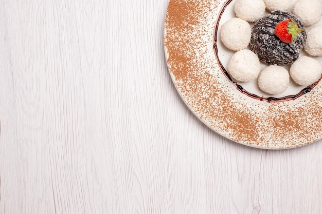 Deliciosos doces de coco com bolo de chocolate no fundo branco bolo de açúcar biscoito doce