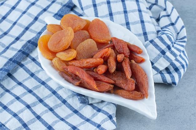 Deliciosos dois tipos de frutas secas, na tigela, na toalha, na mesa de mármore.
