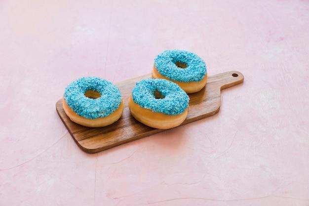 Deliciosos donuts azuis na tábua de madeira