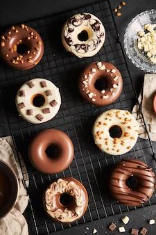 Deliciosos donuts cobertos com cobertura de chocolate com os ingredientes em uma mesa