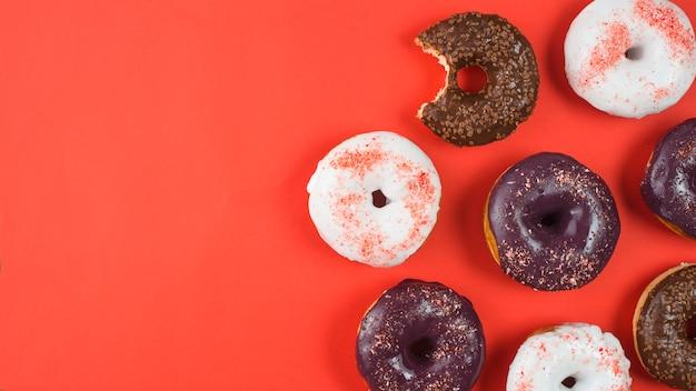 Deliciosos donuts com cobertura e falta de mordida no fundo vermelho