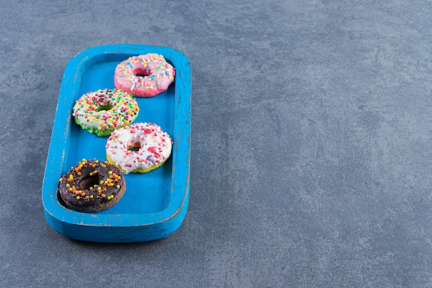Deliciosos donuts com cobertura em uma placa na superfície de mármore