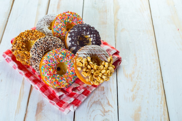 Deliciosos donuts com cobertura na chapa de madeira