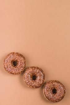 Deliciosos donuts com cobertura no fundo marrom