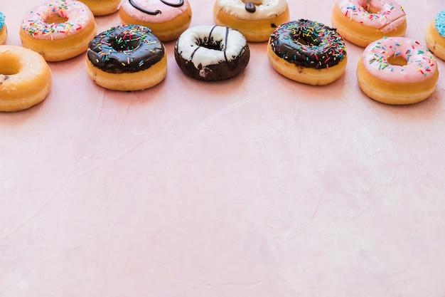 Deliciosos donuts frescos no pano de fundo rosa