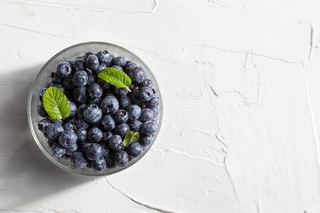 Deliciosos e apetitosos frutos de mirtilo em uma tigela e folhas de hortelã hortelã-pimenta na superfície texturizada branca vista superior com espaço de cópia
