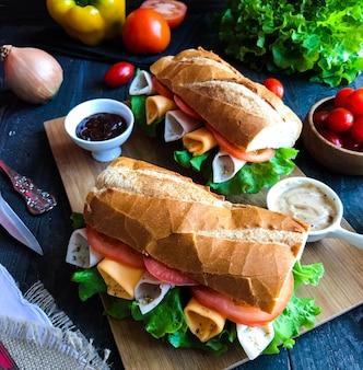 Deliciosos e saborosos sanduíches com peru, presunto, queijo, tomate