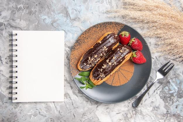 Deliciosos eclairs de chocolate com morangos em um bolo de biscoitos de sobremesa de mesa clara