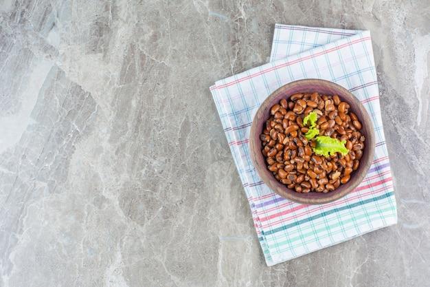 Deliciosos feijões cozidos em uma tigela no pano de prato em mármore.