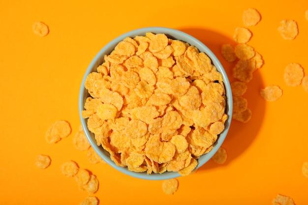 Deliciosos flocos de milho em um prato contra um fundo colorido