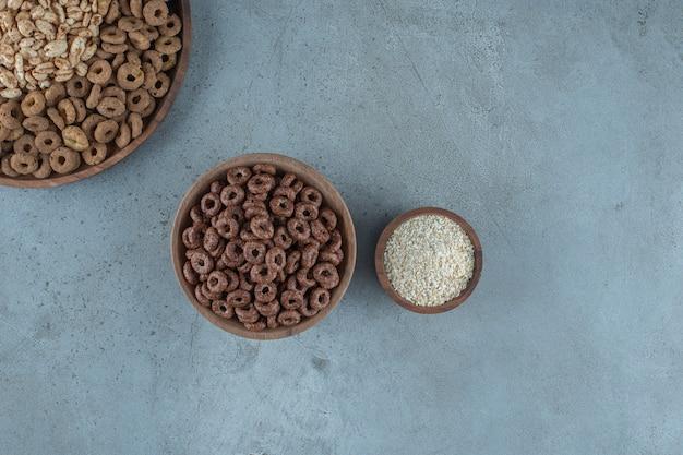 Deliciosos flocos de milho nas tigelas de madeira, no fundo azul.