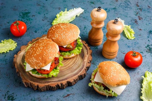 Deliciosos hambúrgueres caseiros frescos no escuro