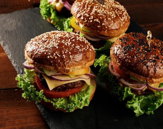 Deliciosos hambúrgueres com costeleta de boi frita, tomate, alface e cebola, pão crocante de farinha de trigo branco com sementes de gergelim.