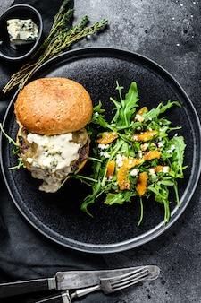 Deliciosos hambúrgueres com queijo azul, bacon, marmelada de carne e cebola marmoreada, um prato de salada com rúcula e laranjas. fundo preto. vista do topo