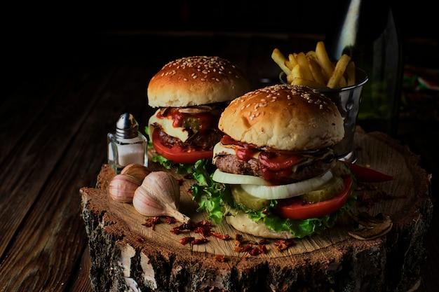 Deliciosos hambúrgueres em estilo rústico, no fundo escuro de madeira.