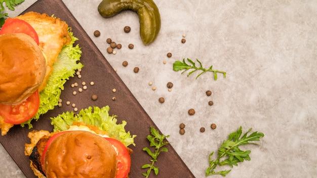 Deliciosos hambúrgueres na mesa cinza