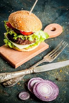 Deliciosos hambúrgueres saborosos frescos com costeleta de carne, legumes frescos e queijo