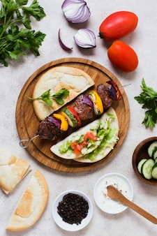 Deliciosos legumes fast-food árabes e carnes em espetos vista superior