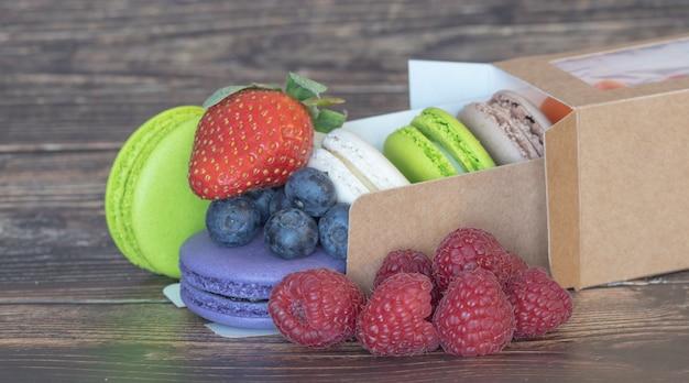Deliciosos macaroons de cores diferentes e frutas silvestres com morangos em uma superfície de madeira