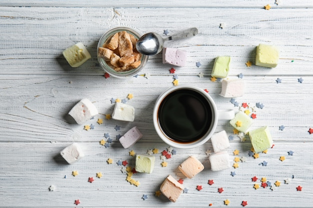 Deliciosos marshmallows e café na madeira branca