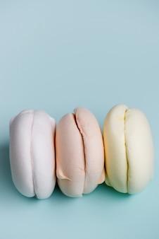 Deliciosos marshmallows em tons pastel, sobre fundo azul. zéfiro de clolrful.